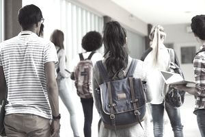 High school students walking down the hall with backpacks.