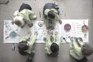 Preschool students using finger paints on poster.