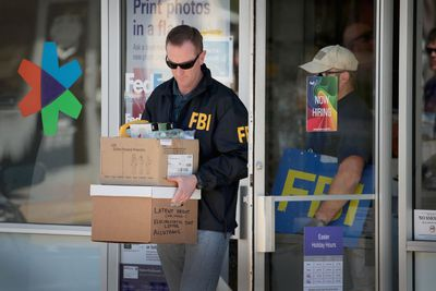 Agent for the FBI removes boxes of equipment from a building