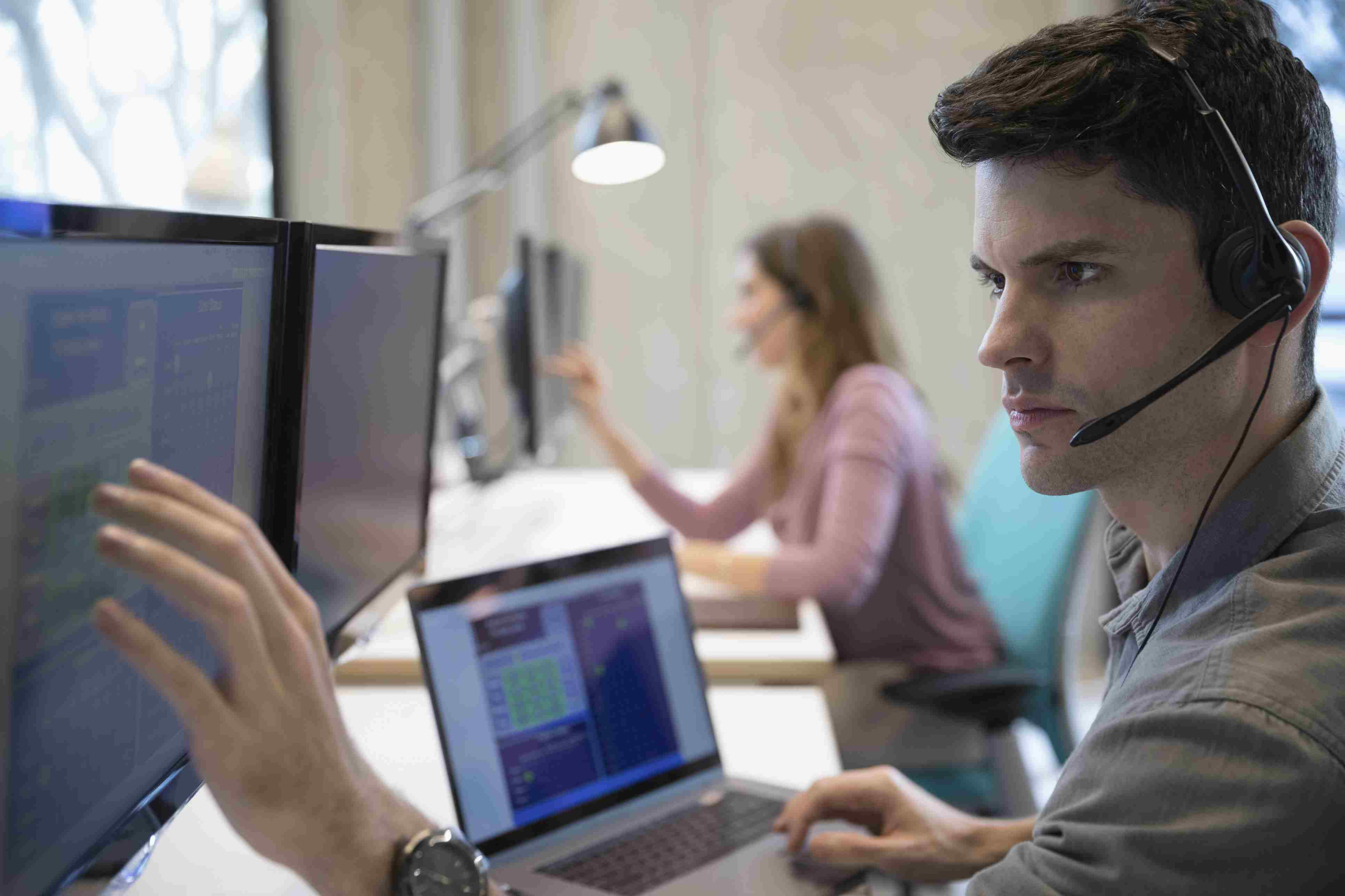 Technical support operator with headset working at laptop and computer