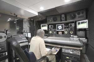 a man sitting at mixing board in a recording studio