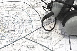 Pilot headset resting on a map.
