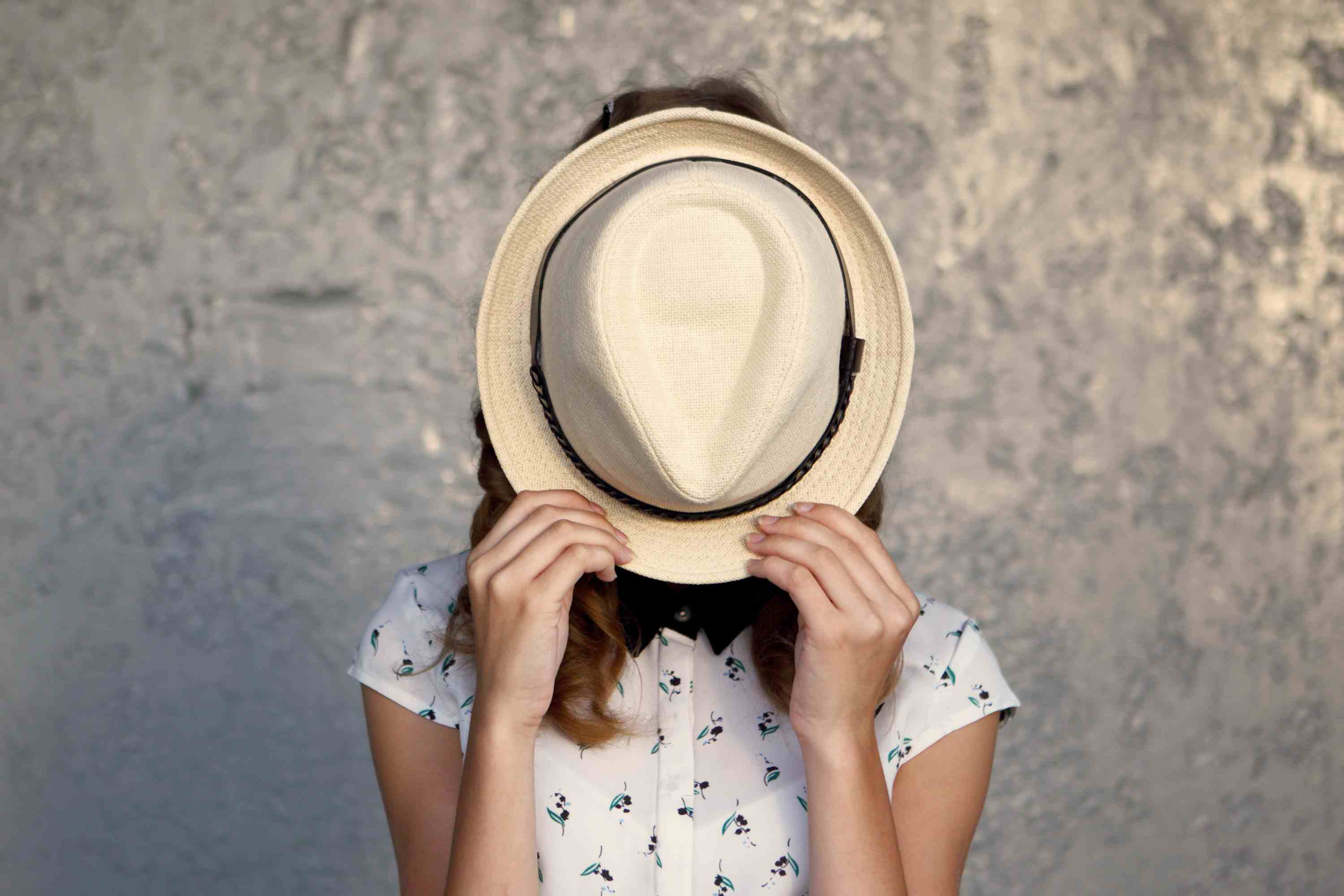 Person with hat in front of their face