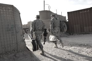Military Chaplains walking into an armed base in Afghanistan to minter to troops.