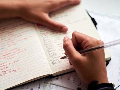 Close-up of hands taking notes of new words in handmade dictionary