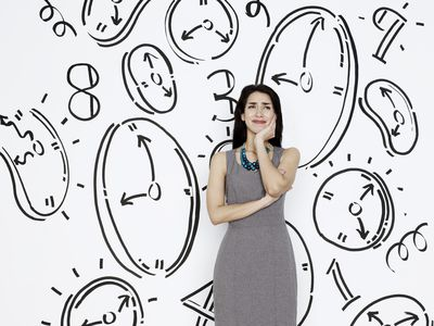 woman standing in front of illustrated wall with representations of time like clocks and numbers