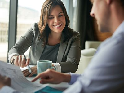 A woman in business attire is pointing out something to a man seated across from her.