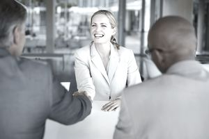 Woman meeting two men, all dressed in formal business attire