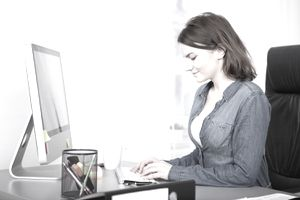 woman writing a resume at a computer