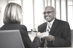 Businesswoman handing a job offer letter to her selected candidate for her open job.