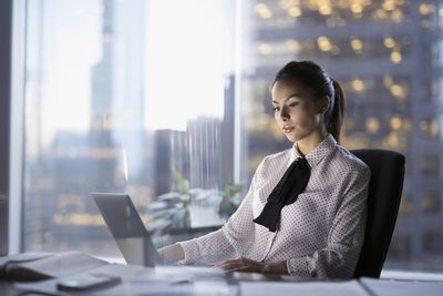 Female lawyer working late at a laptop in an urban office