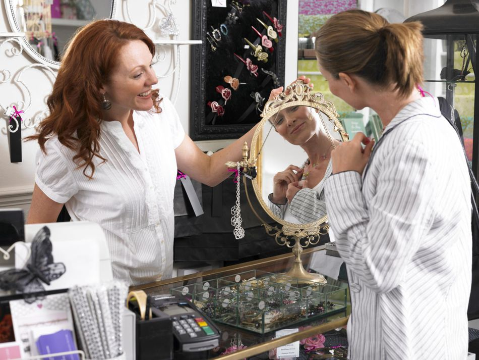 Young woman sales clerk in shop holding mirror, serving customer trying on jewelry