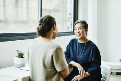 Smiling senior businesswoman in discussion with client in office conference room