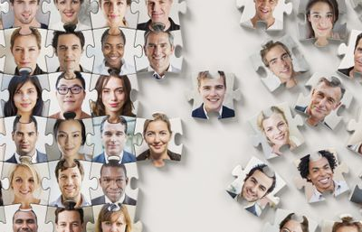 Puzzle made from faces, half completed, representing the concept of outsourcing.