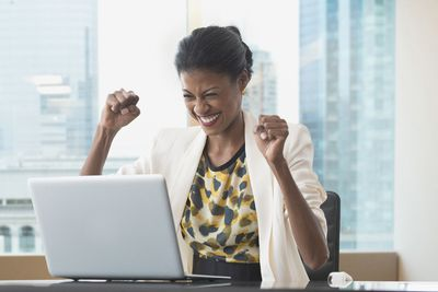 Woman cheering in front of a laptop at the office