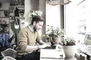 Young Man Sitting In Café Using Laptop