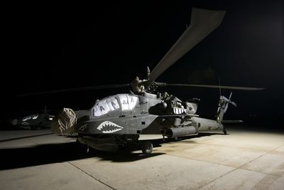 Maintenance crew work on an AH-64D Apache Longbow at night on a military base in Iraq.