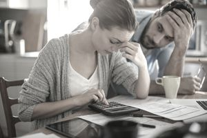 couple looking distressed with bills in front of them