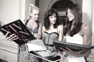 three female models looking at portfolios