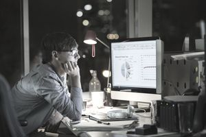 Young analyst working at office computer at night