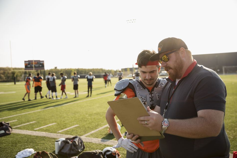 Coach and teenage boy high school football player reviewing game plan on clipboard on sunny football field