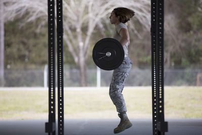 Female soldier jumping with barbell at military air force base