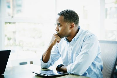 Businessman with digital tablet sitting in office