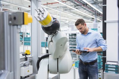 Man using tablet next to assembly robot in factory shop floor