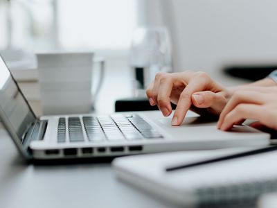 Close up image of woman's hand working on laptop in office.