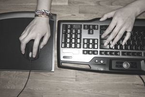 a young person's hands with mouse and keyboard shot from above
