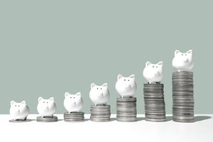 Little piggy banks standing on top of stacks of coins in ascending order