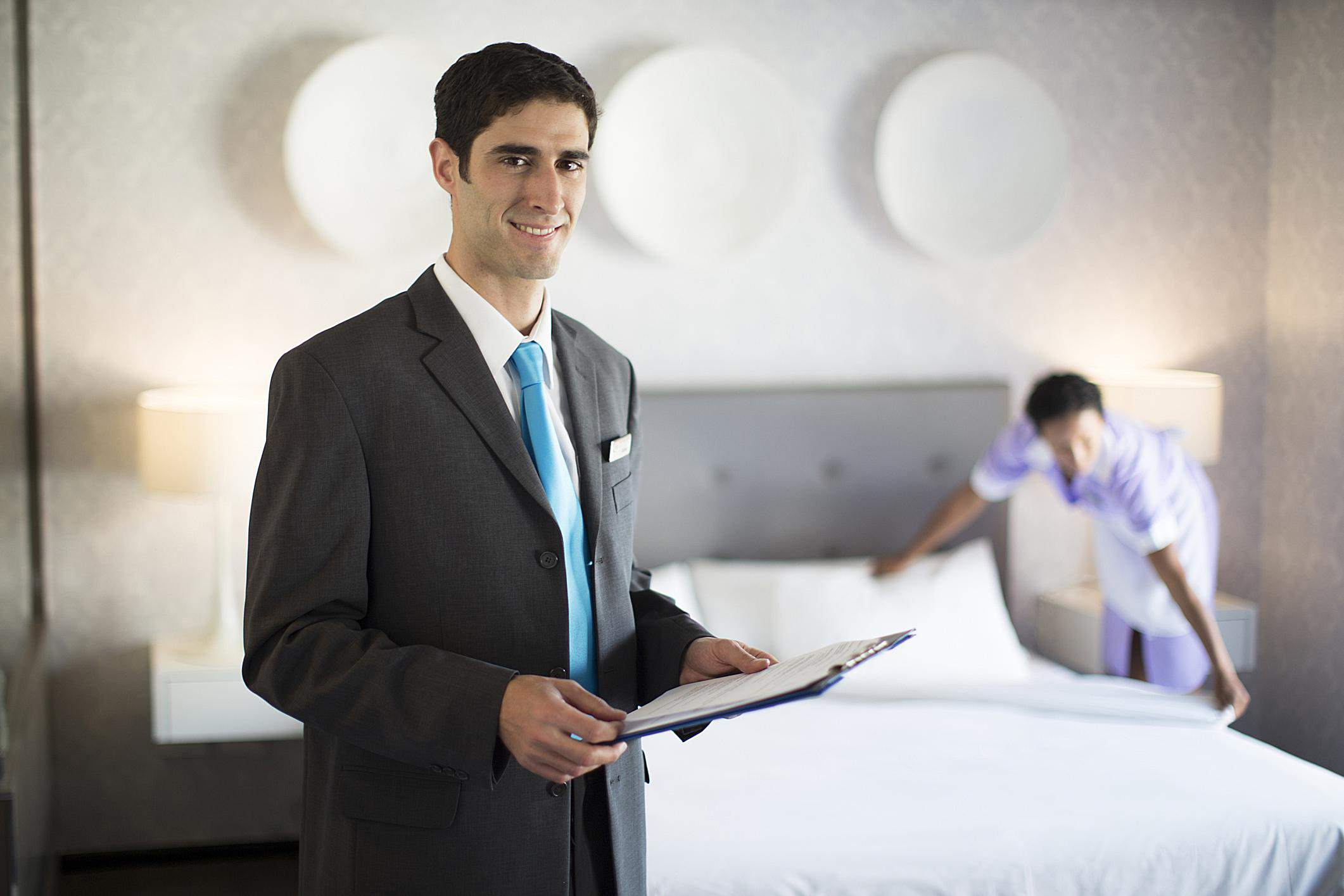 Concierge overseeing the cleaning of a hotel room