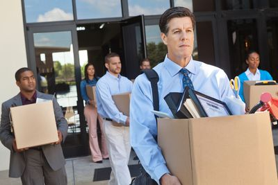Group of professionals leaving office after a layoff