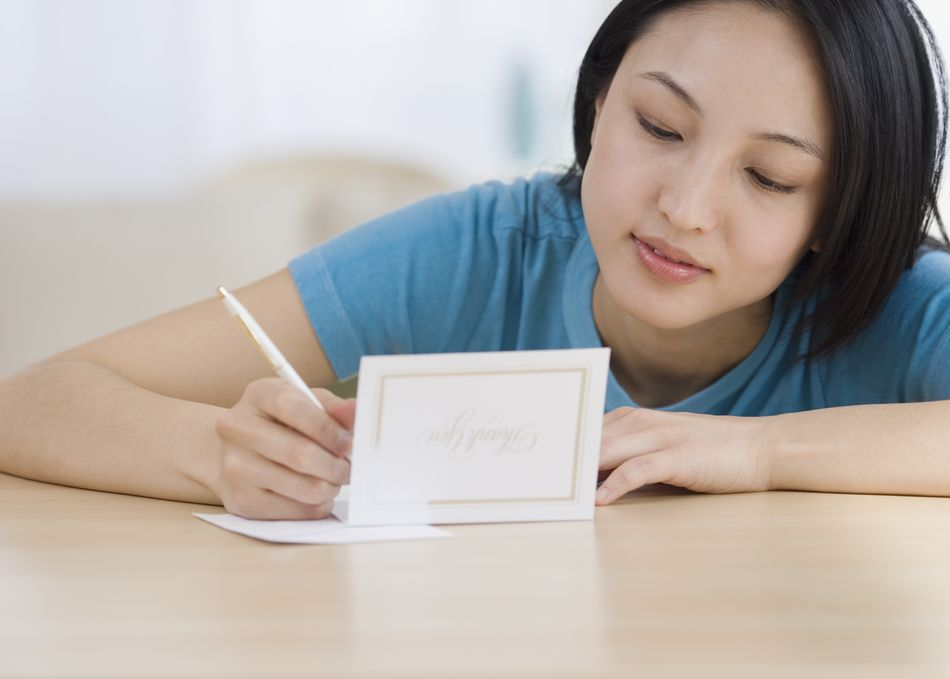 Asian woman writing thank you card