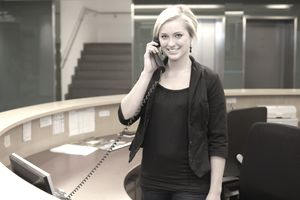 A young business woman at a reception desk.