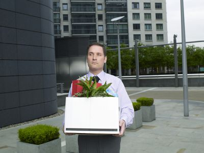 A dismissed employee leaves work with a box of belongings