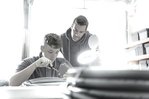 Apprentice and electrical engineer mentor in cable finishing factory