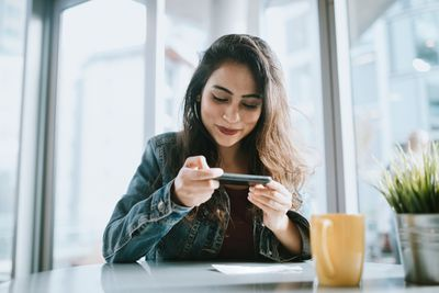 A woman uses her smartphone to electronically deposit her bonus check.