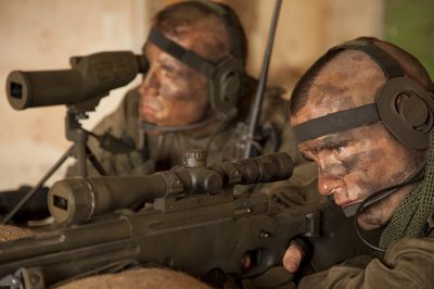 Army Special Operation Forces sniper and spotter in the field with camouflaged faces.