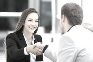 Happy woman shaking hands with man