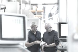 Engineers inspecting complex metal component in factory