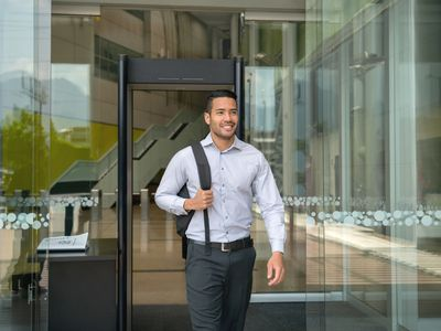 Handsome young businessman leaving a business center holding his backback very happy