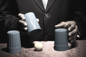 A man playing a shell game with three cups on a table.