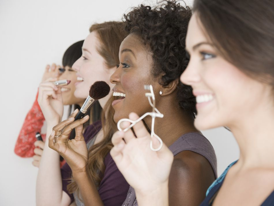 a group of women doing their makeup