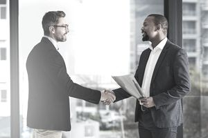 Two businessmen shaking hands in an office building