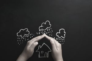 Home Insurance Concept Child protecting a house drawn on a chalkboard with their hands.