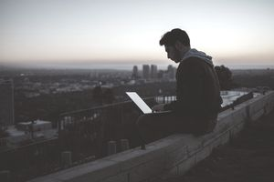 Man sitting on rooftop at sunset taking an aptitude test on his laptop.