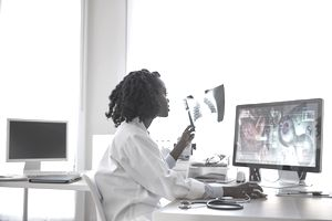female doctor who specializes in x-rays looking at an x-ray scan and computer screen