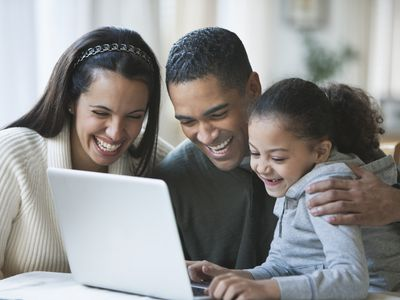 Parents on sabbatical leave spending time with their daughter watching a video on a laptop.