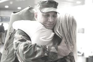 Returning soldier hugging wife in airport